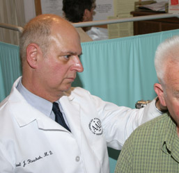 Paul J. Ruschak, M.D., conducts a skin screening photo
