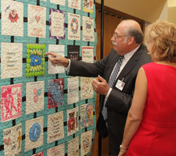 Monongahela Valley Hospital President and CEO Louis J. Panza Jr. examines the Intensive Care Unit quilt square photo