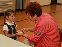 Auxilian Gail Jericho cleans the hands of kindergarten student photo
